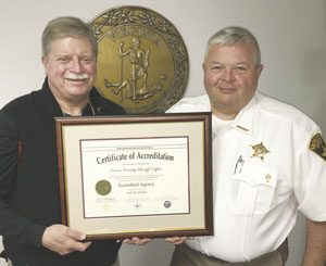 Sheriff Steve Smith (right) and Deputy Mike Martin display the Sheriff's Office certificate of accreditation.
